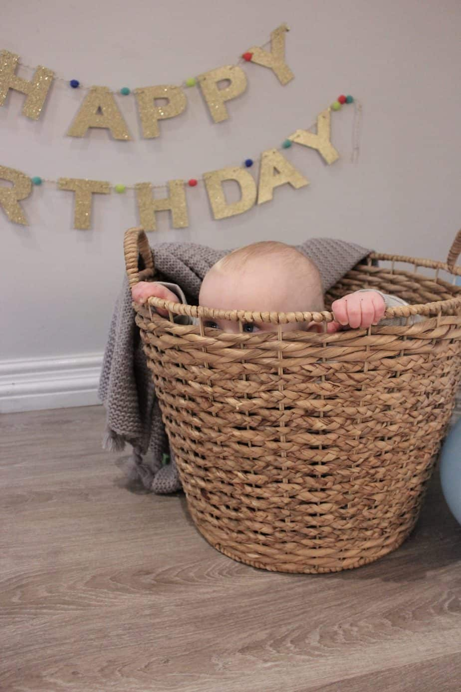 Baby K is peek a boo from the wicker basket on his cake smash shoot