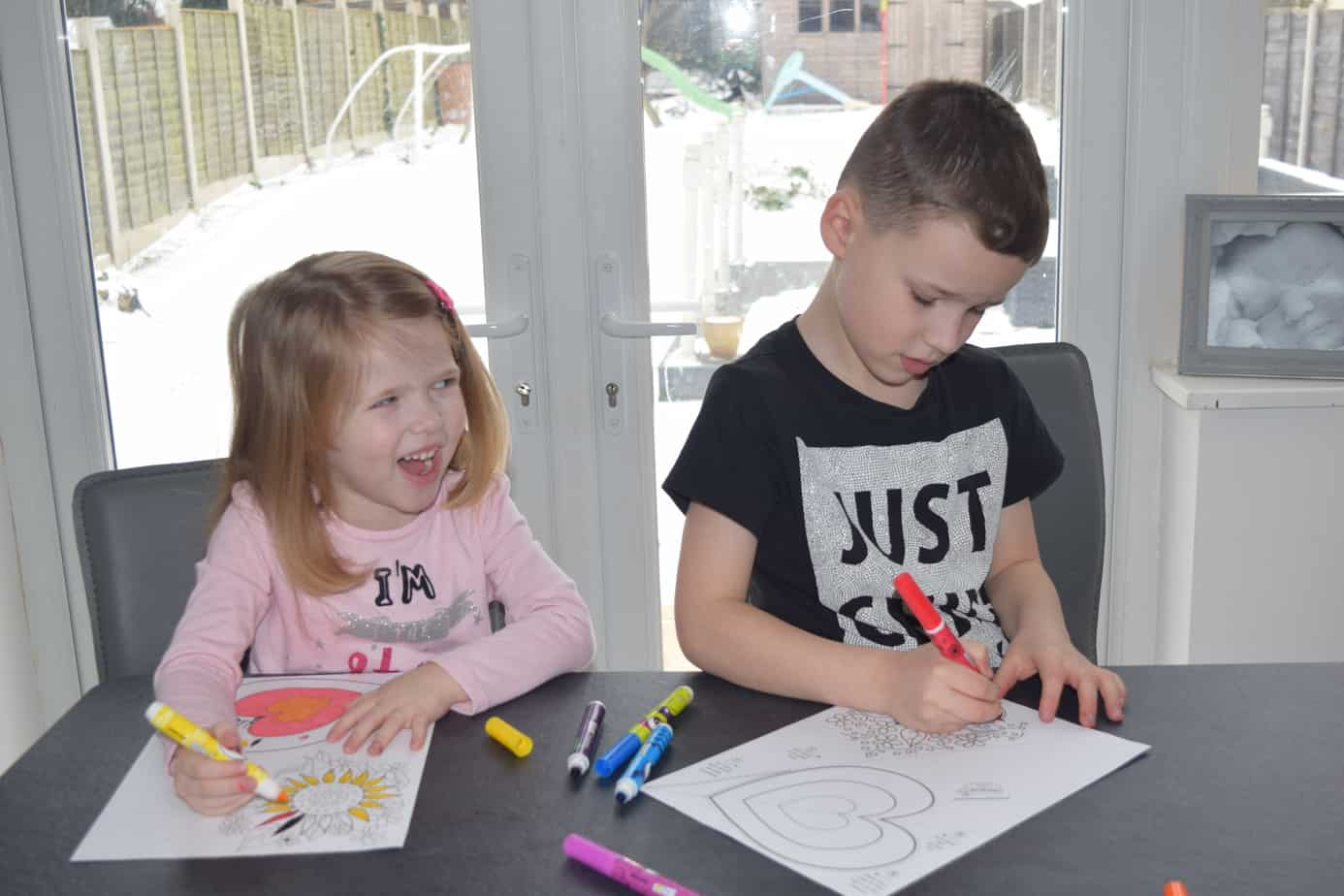 The children laughing together while enjoying their colouring