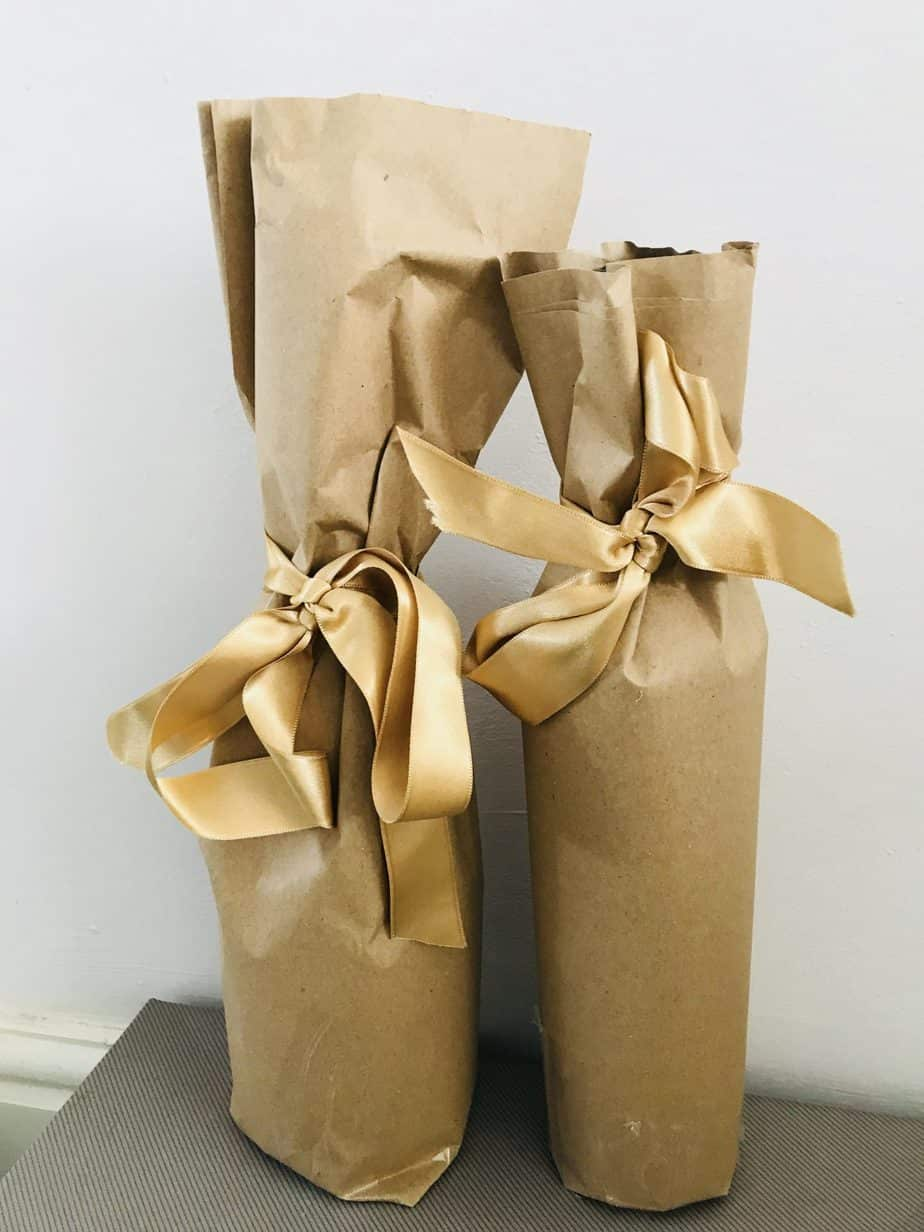 Wrapped up bottles of slimline wine in brown paper and gold bows