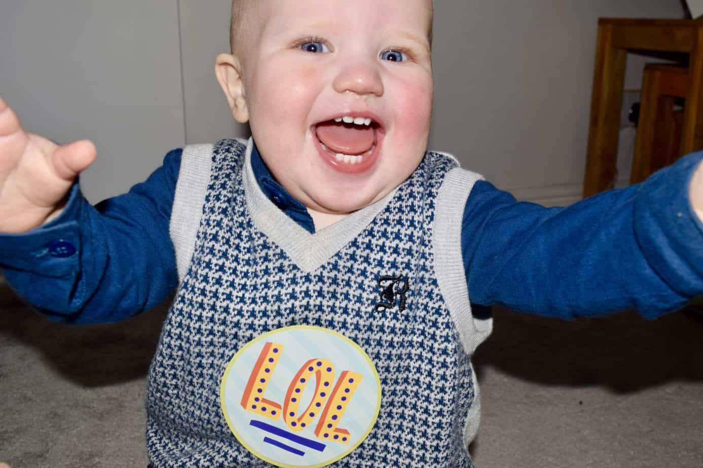 Baby K smiling at the camera with a LOL sticker on him