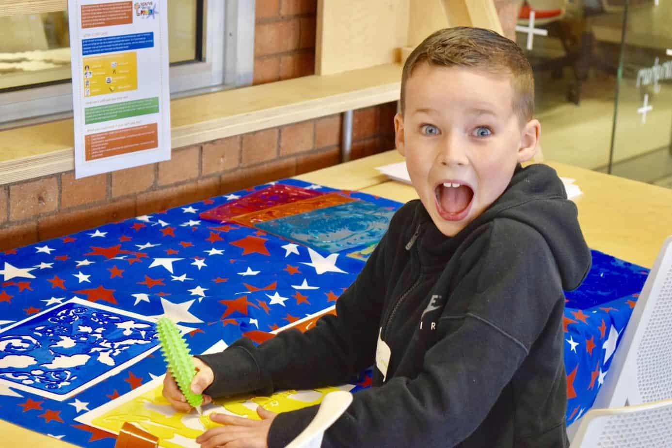 B enjoying some writing and colouring at Playfest at Impact Hub birmingham