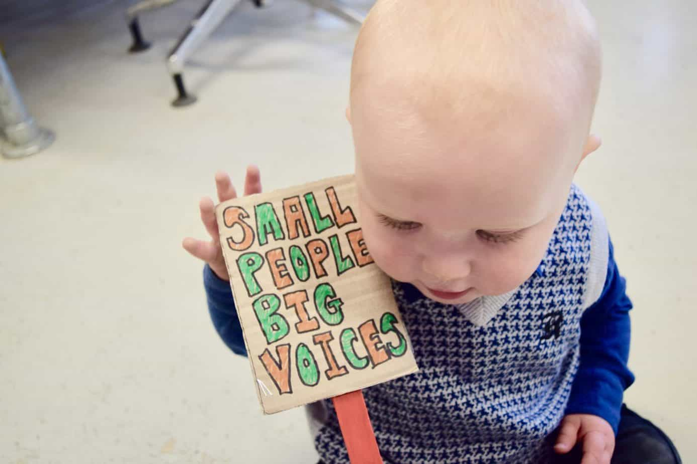 Baby K holding a sign reading 'Small people big voices