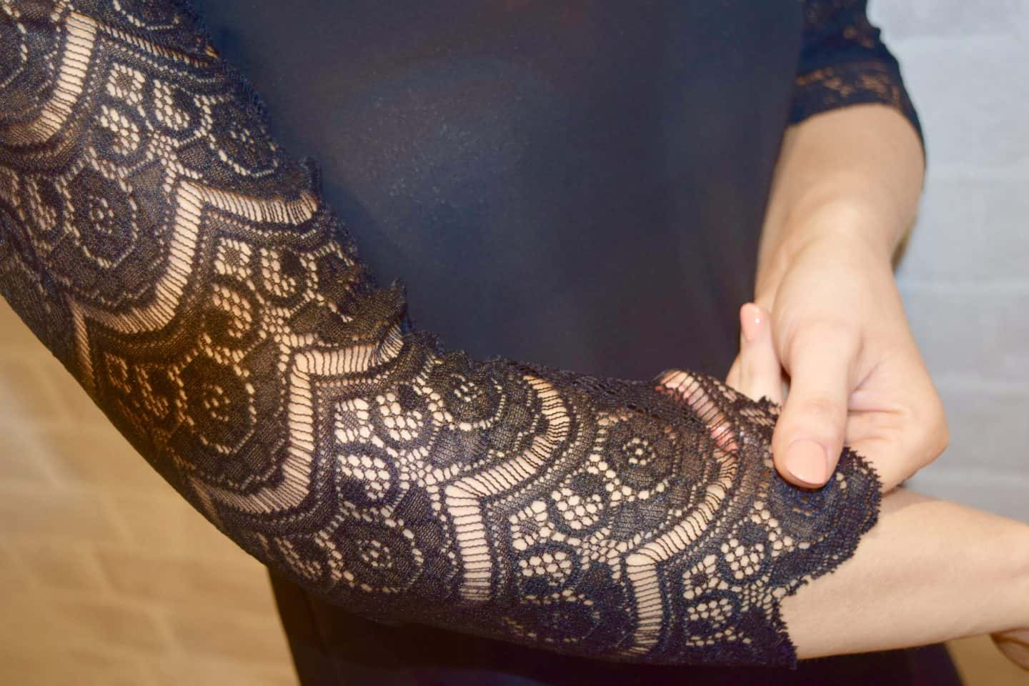 A close up of the sleeves in black lace