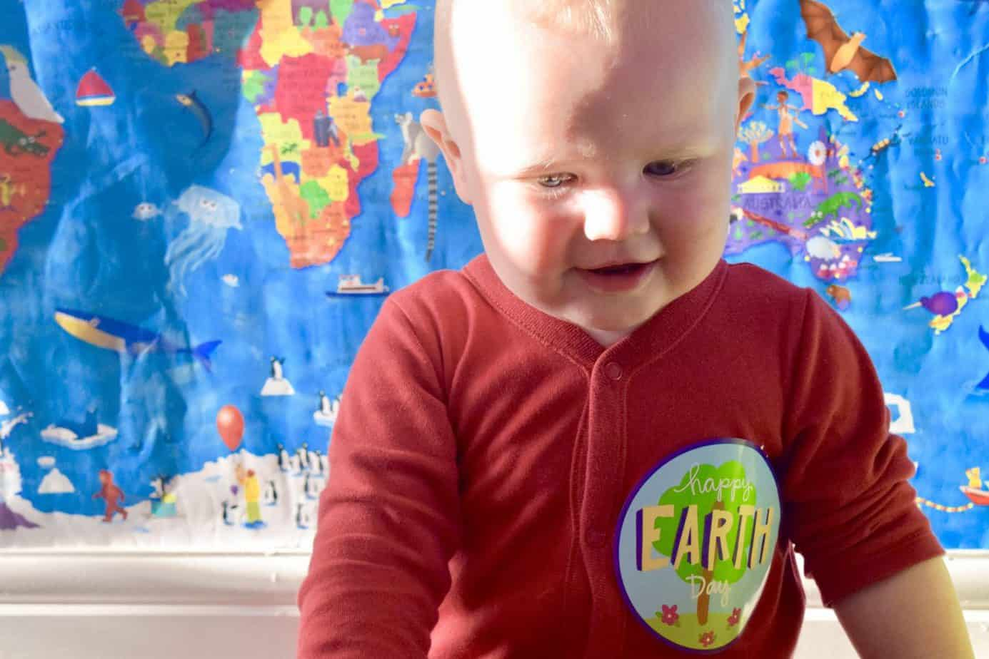 Baby K wearing an Happy Earth Day belly sticker in front of a picture of a map