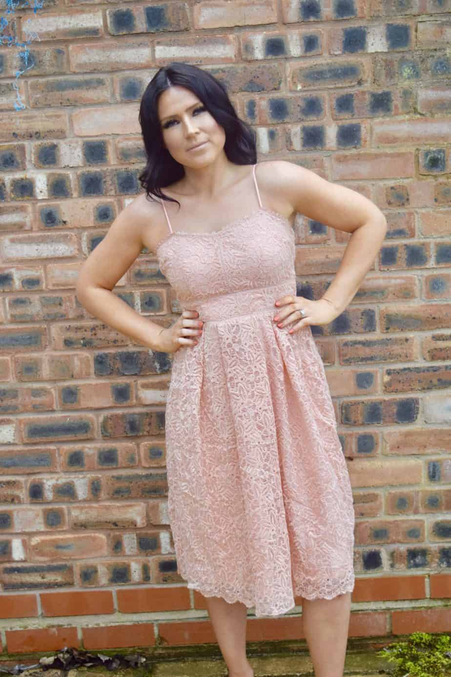 Standing infront of a brick wall wearing Boohoo occasional dress for a wedding