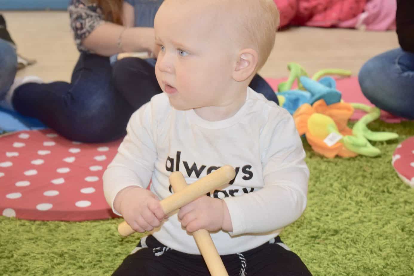 Baby K playing with wooden sticks during or Hartbeeps class