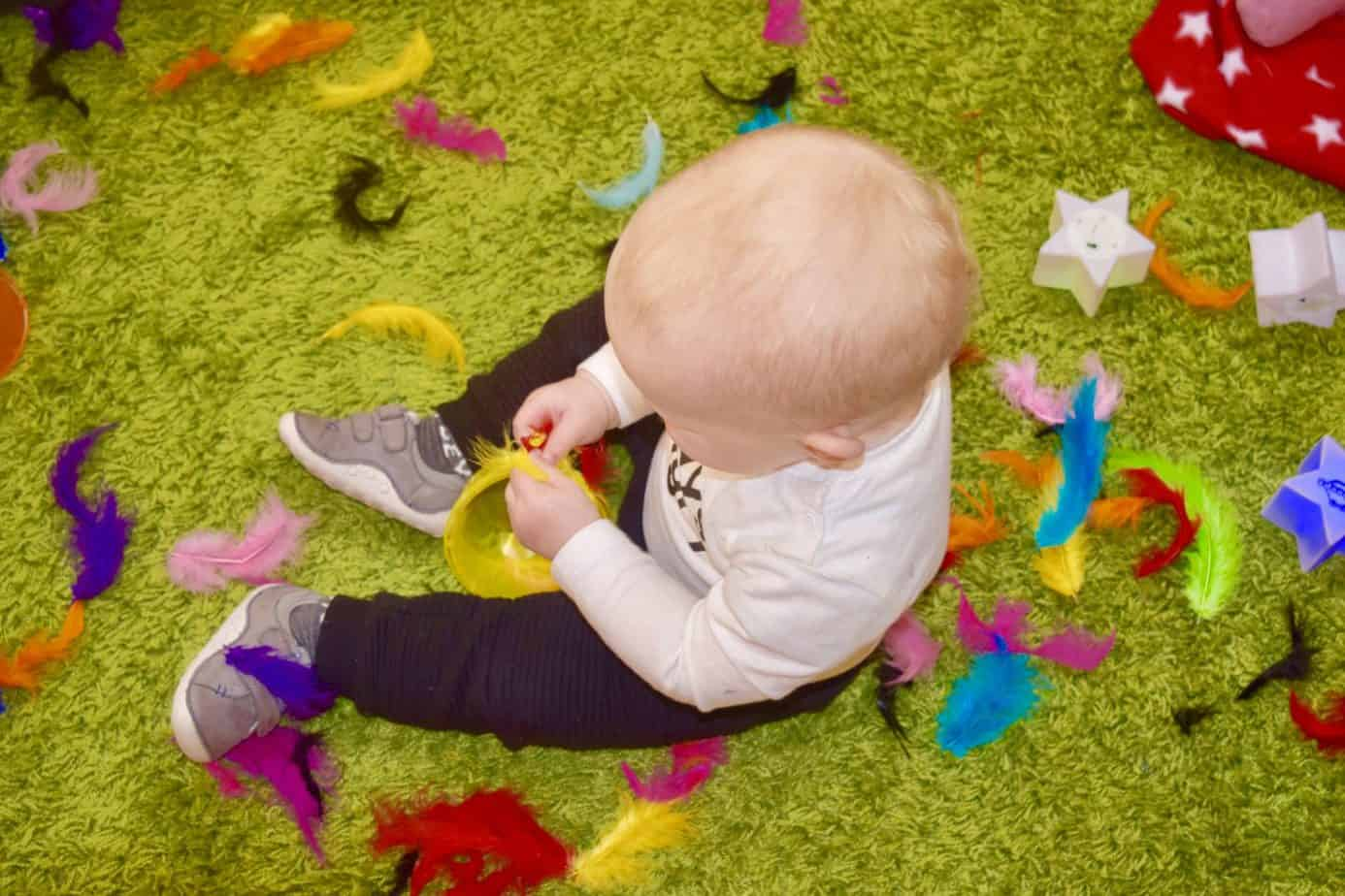 Baby K surrounded by colourful feathers during our time at hart beeps