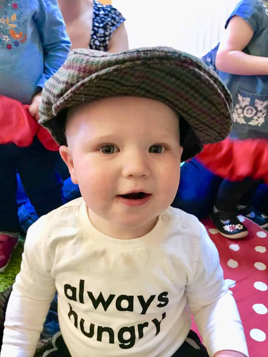 Baby K wearing a flat cap pretending to be on a tractor