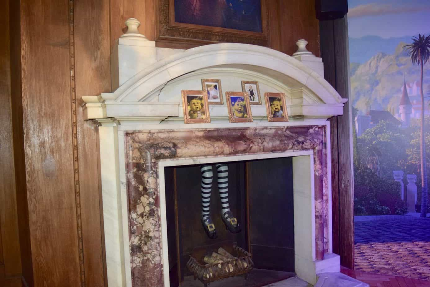 A fireplace with legs coming down from the chimney at Shrek's Adventure