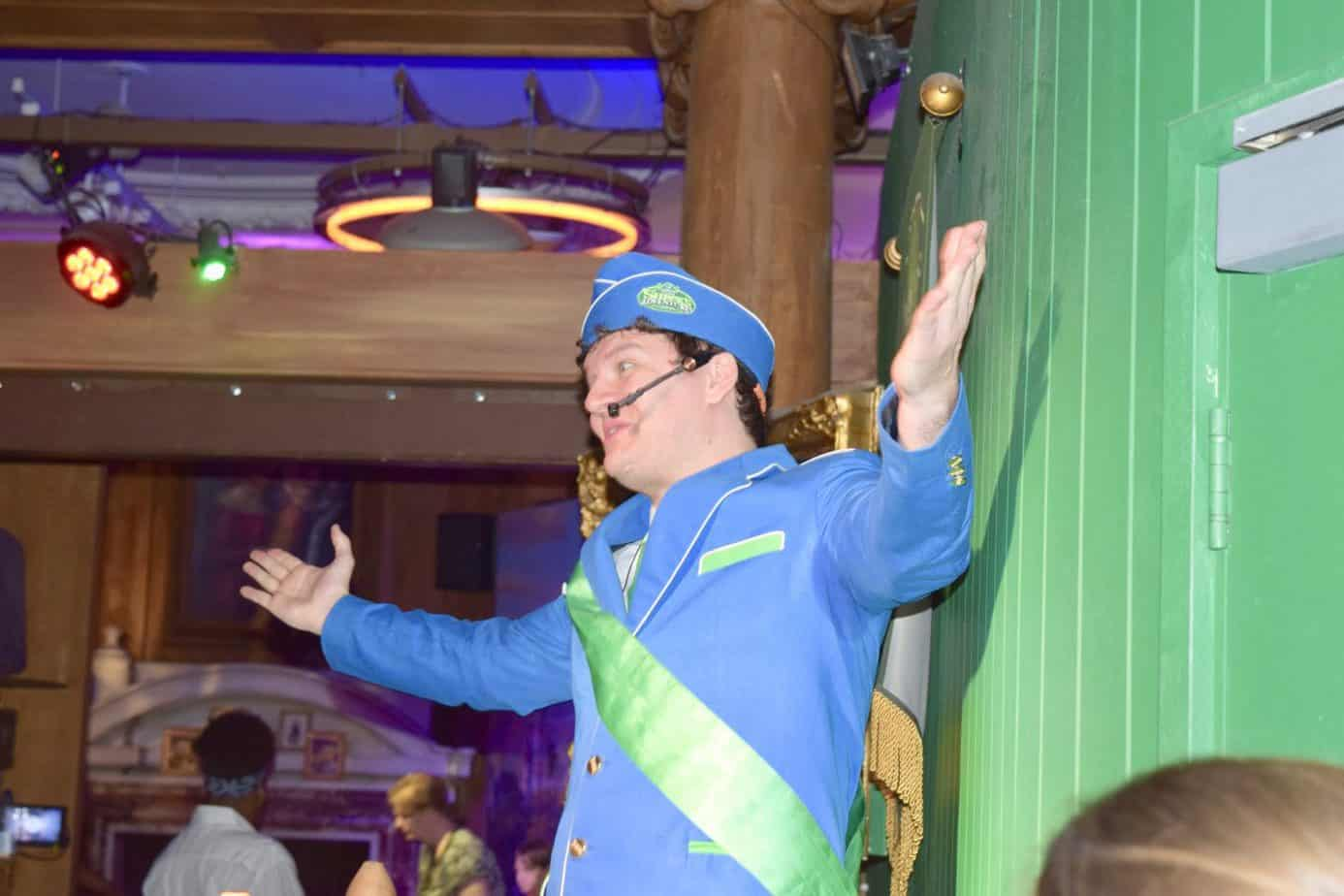 A staff member seating an air steward outfit wishing us on to our Shrek's Adventure tour