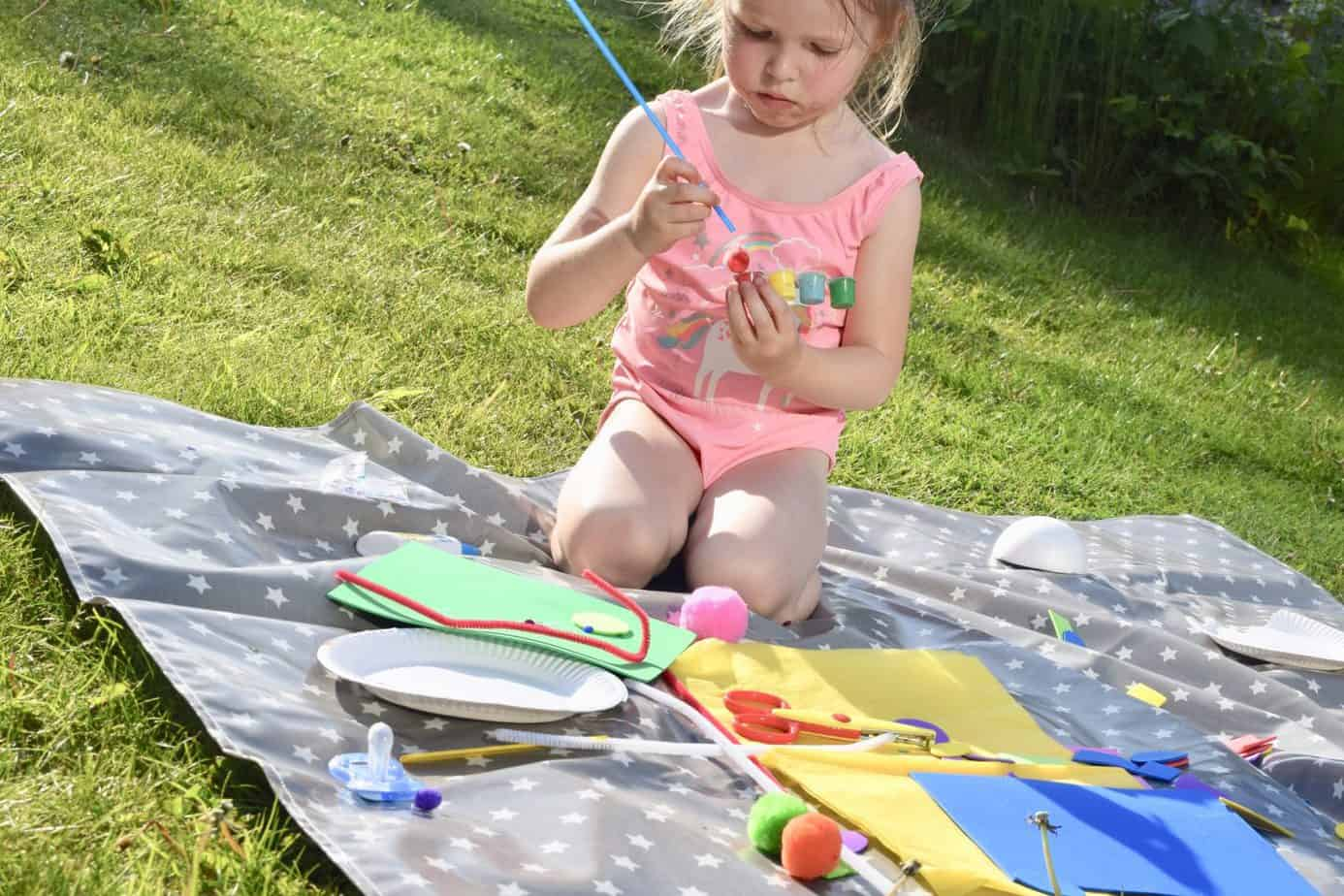 W on the messy me splash mat painting in the garden