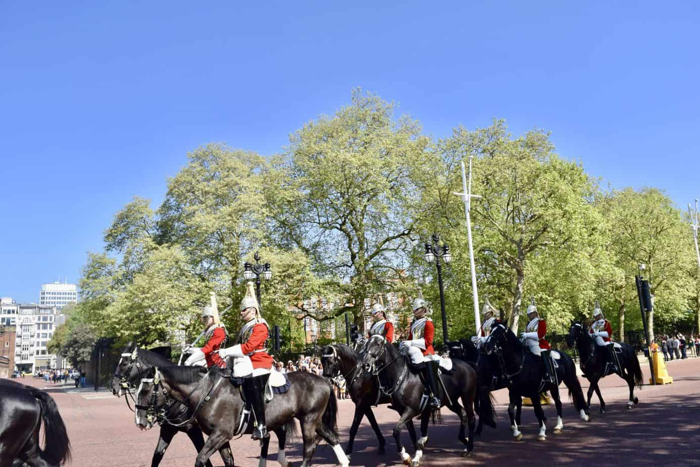 Changing of the guards with the guards on their horses entering Buckingham places available with a free walking tour