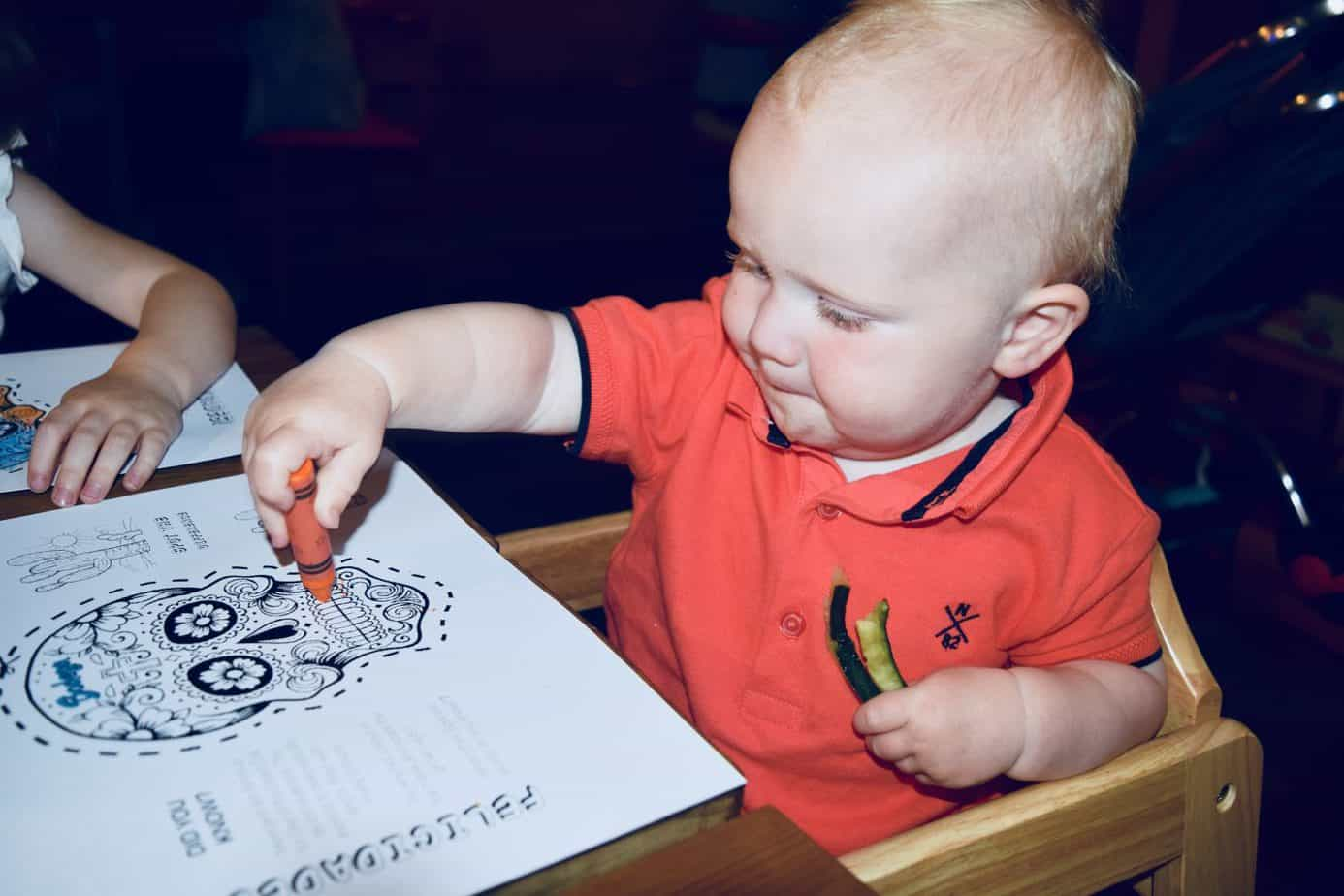 A happy Baby K doing some colouring