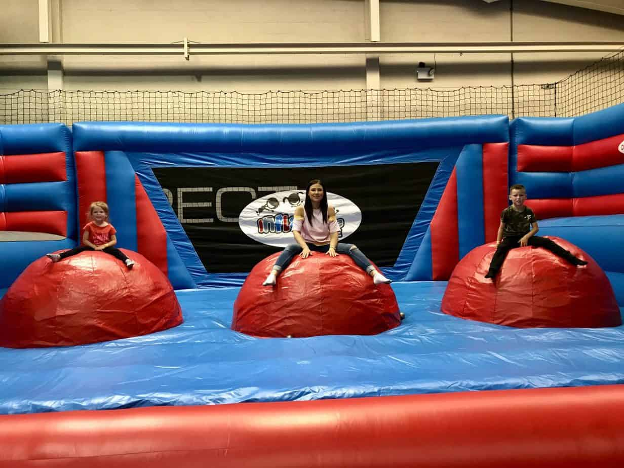 W, B and I sitting on the wrecking balls at Inflatable zone, an activity offered by Buckt