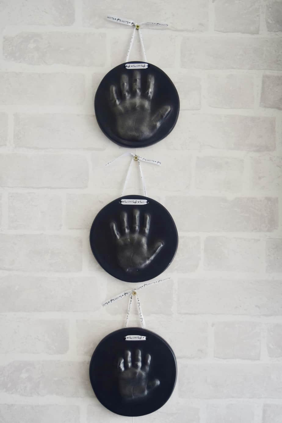 My three children's imprints hanging on the wall in a vertical line made by Blossom Keepsakes