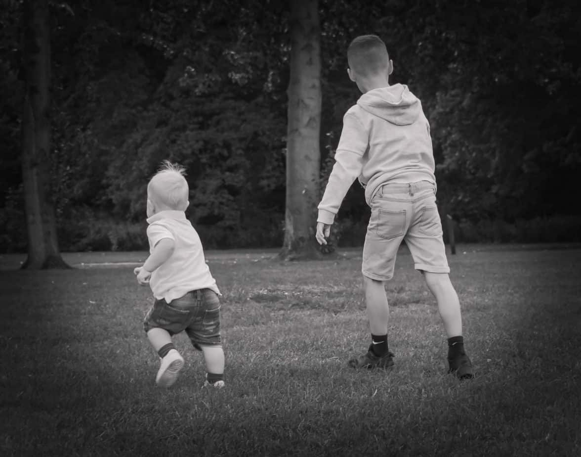 Black and white phot of B and Baby K running away on the grass taken by Everlasting Memories Photography UK