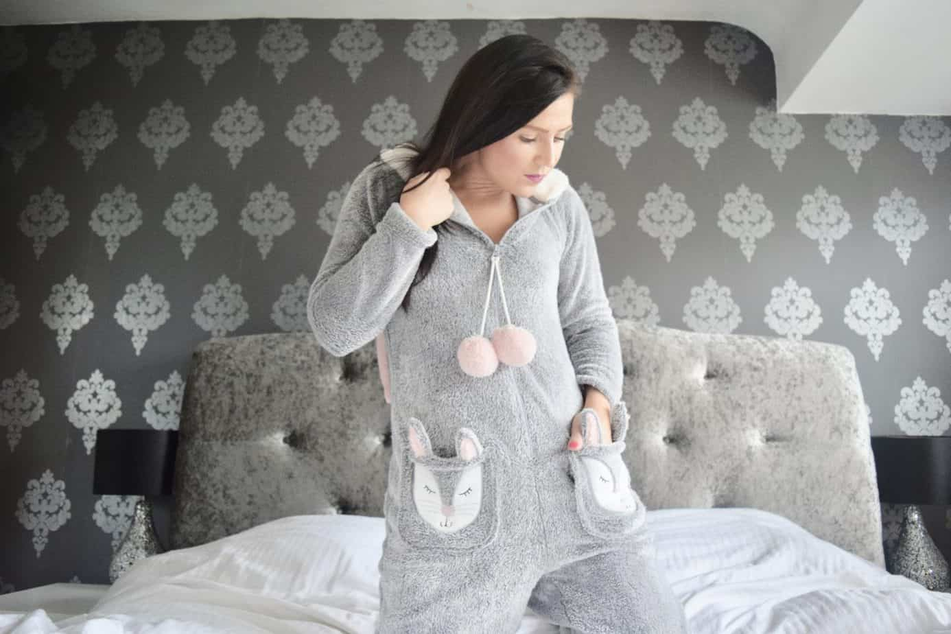 I am kneeling on the bed with my hand on one of the rabbit pockets - onesie made by Hunkemoller