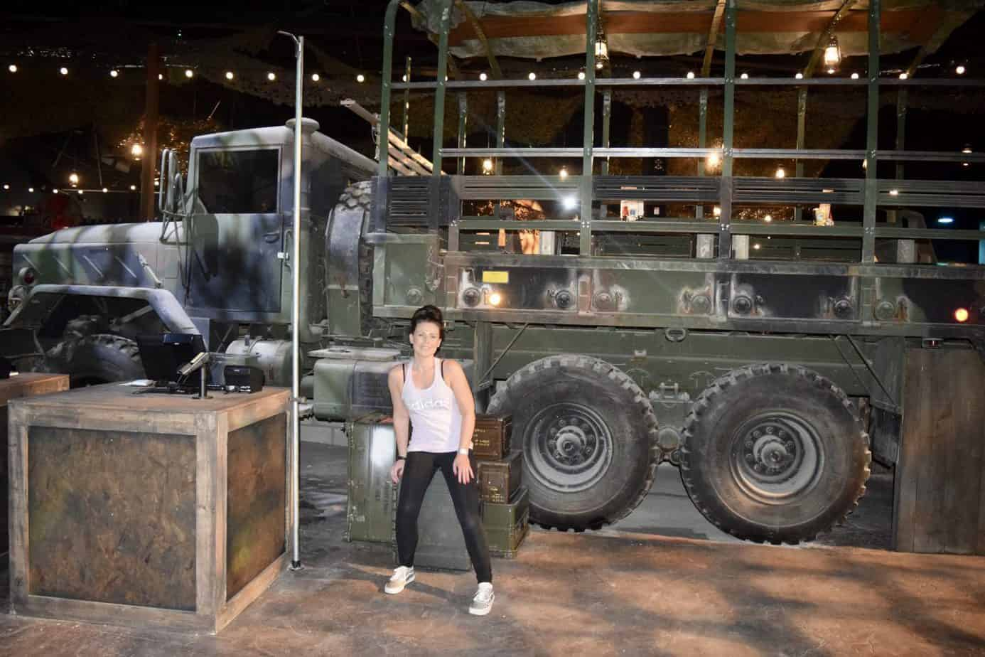 Me outside a huge army truck in the foyer of the bear grylls adventure
