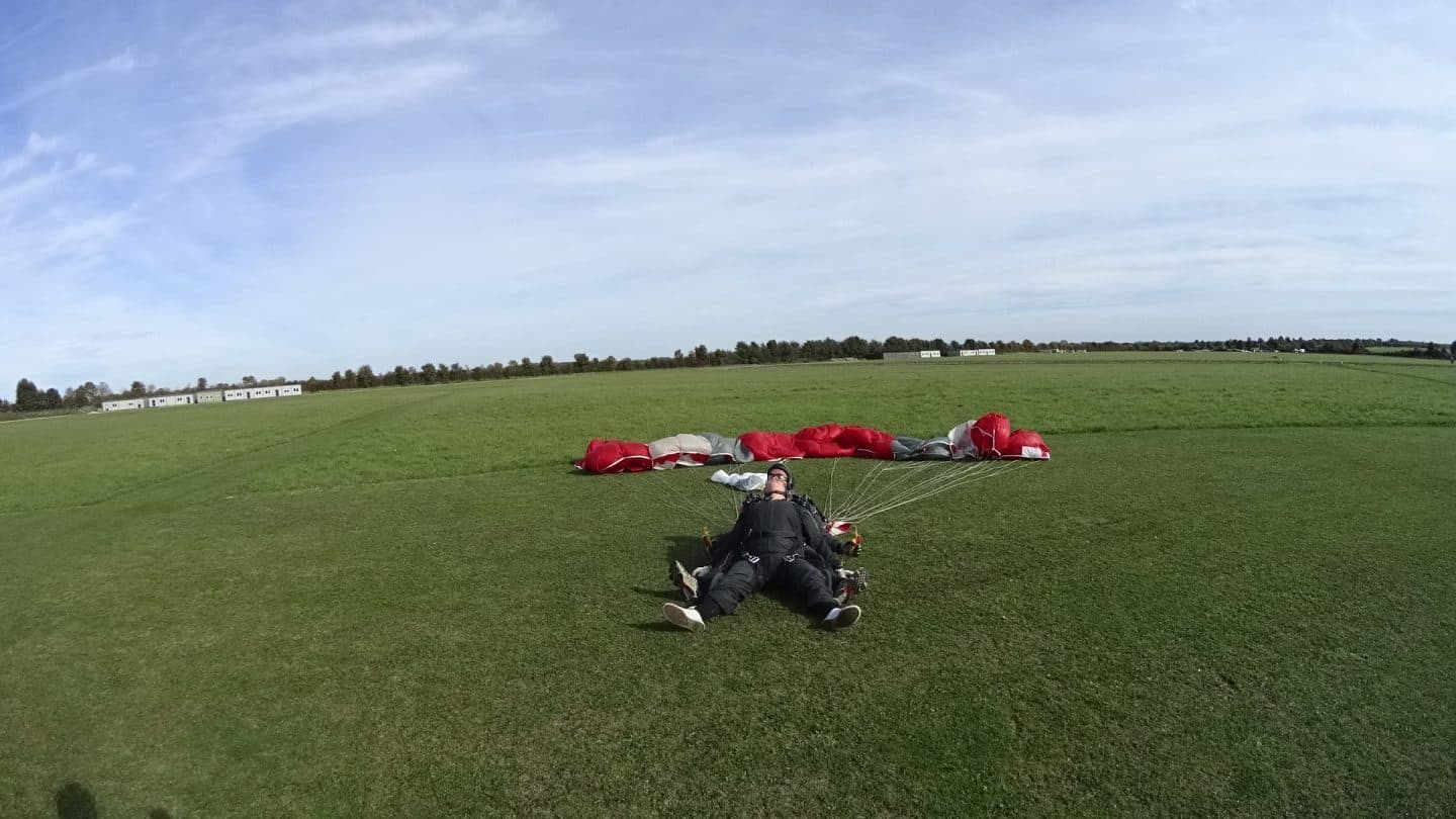 Claire landed and is lying back on her tandem skydiver with relief