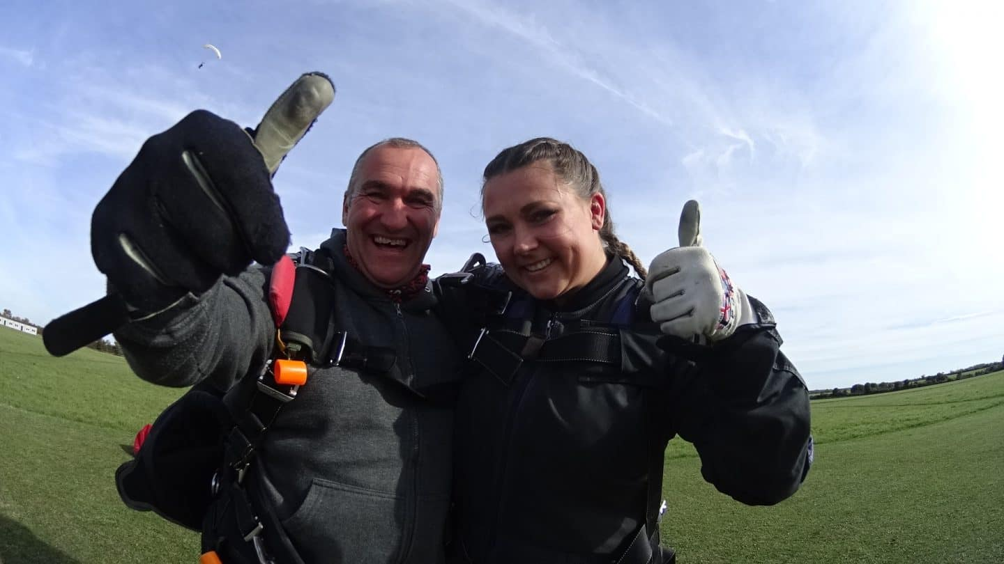Claire and her tandem skydiver thumbs up to the camera and smiling