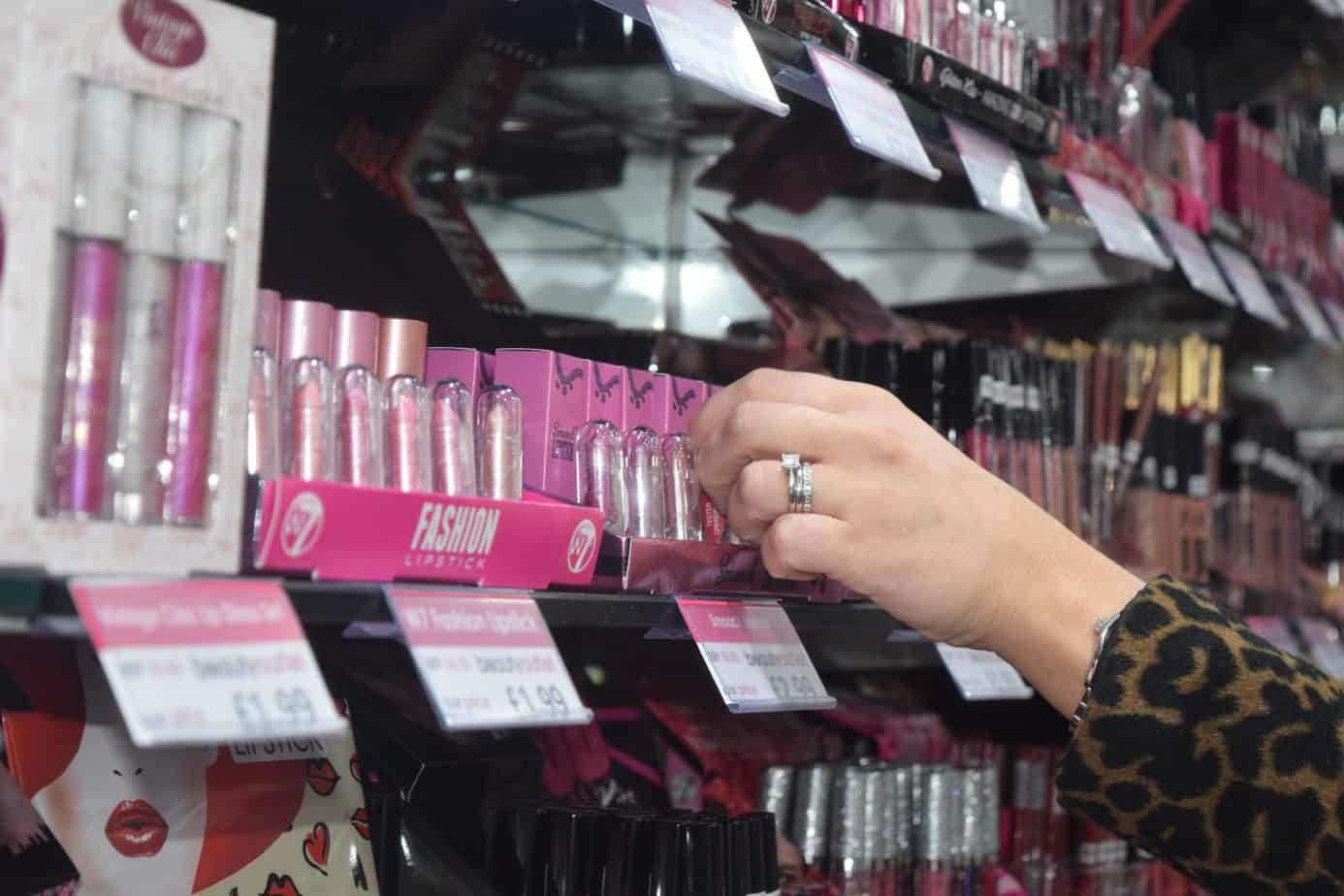 A close up of my hand selecting some lip glosses from the store