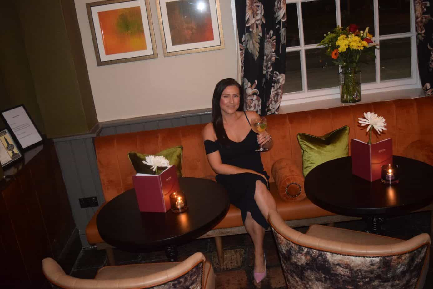 Me smiling holding my gin in the seating area of the bar area in the Bulls Head in Meriden