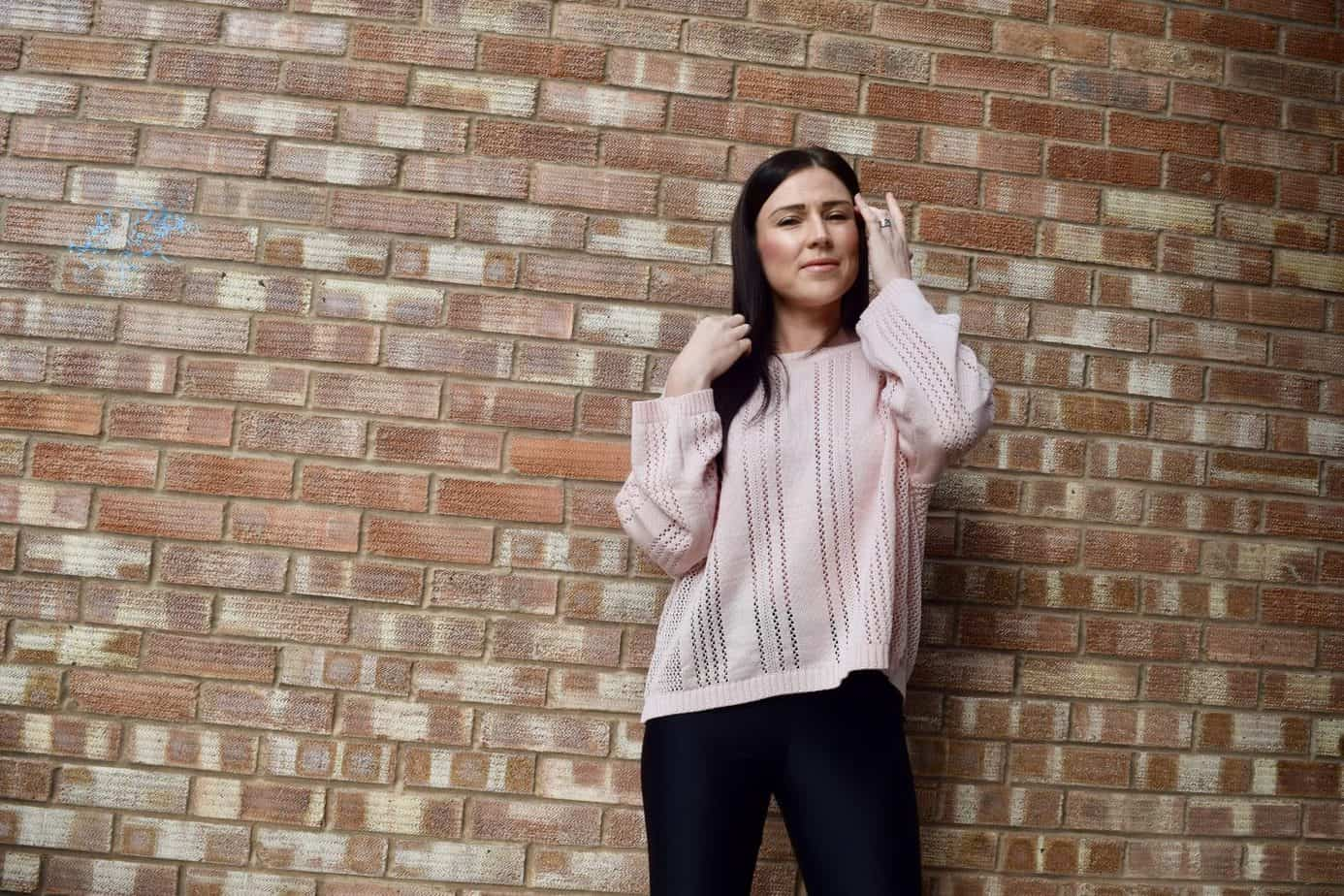 Me wearing my pink jumper from femme luxe against a brick wall smiling at the camera