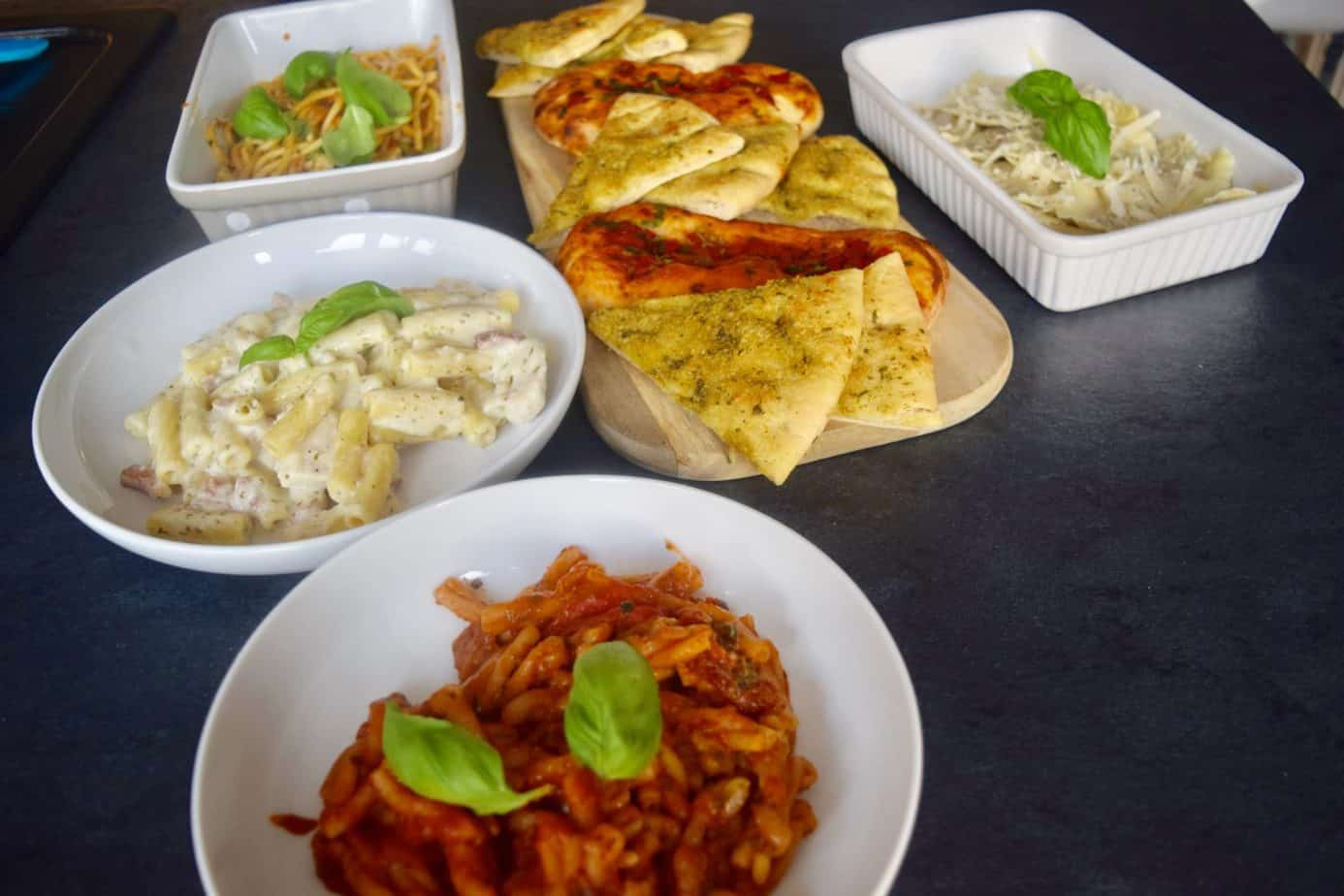 The dishes cooked in their pots laid out on the breakfast bar Marks and Spencer's italian range