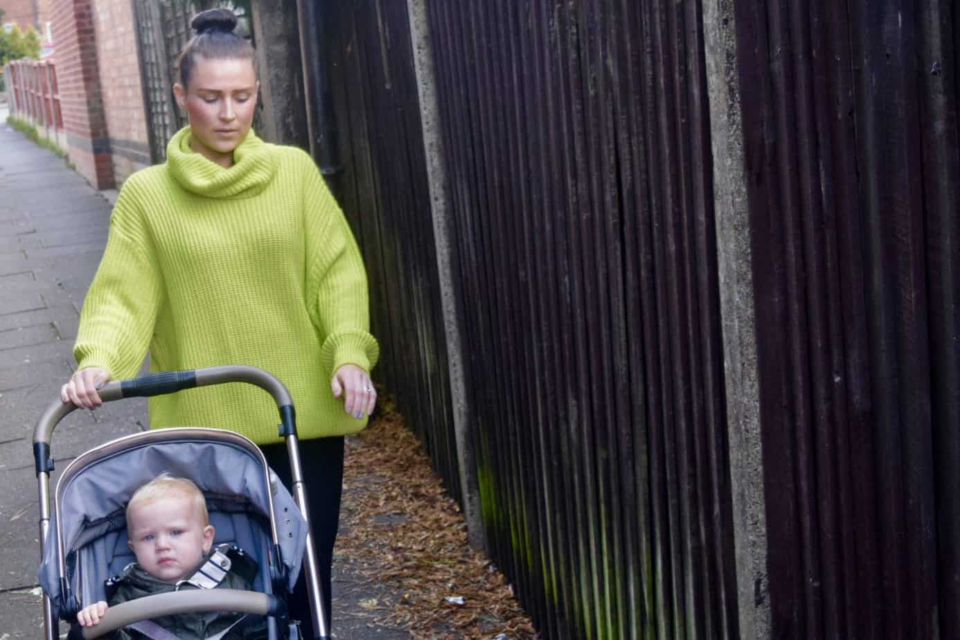 Me walking down an alley way pushing Baby K wearing my chunky knit jumper from the autumn wear at Femme Luxe