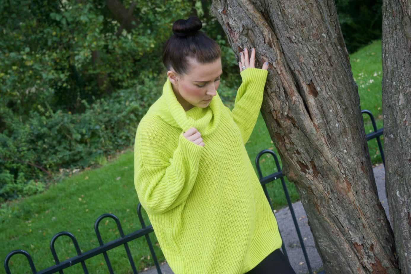 Me looking down holding the polo neck cuff of my chunky knit jumper