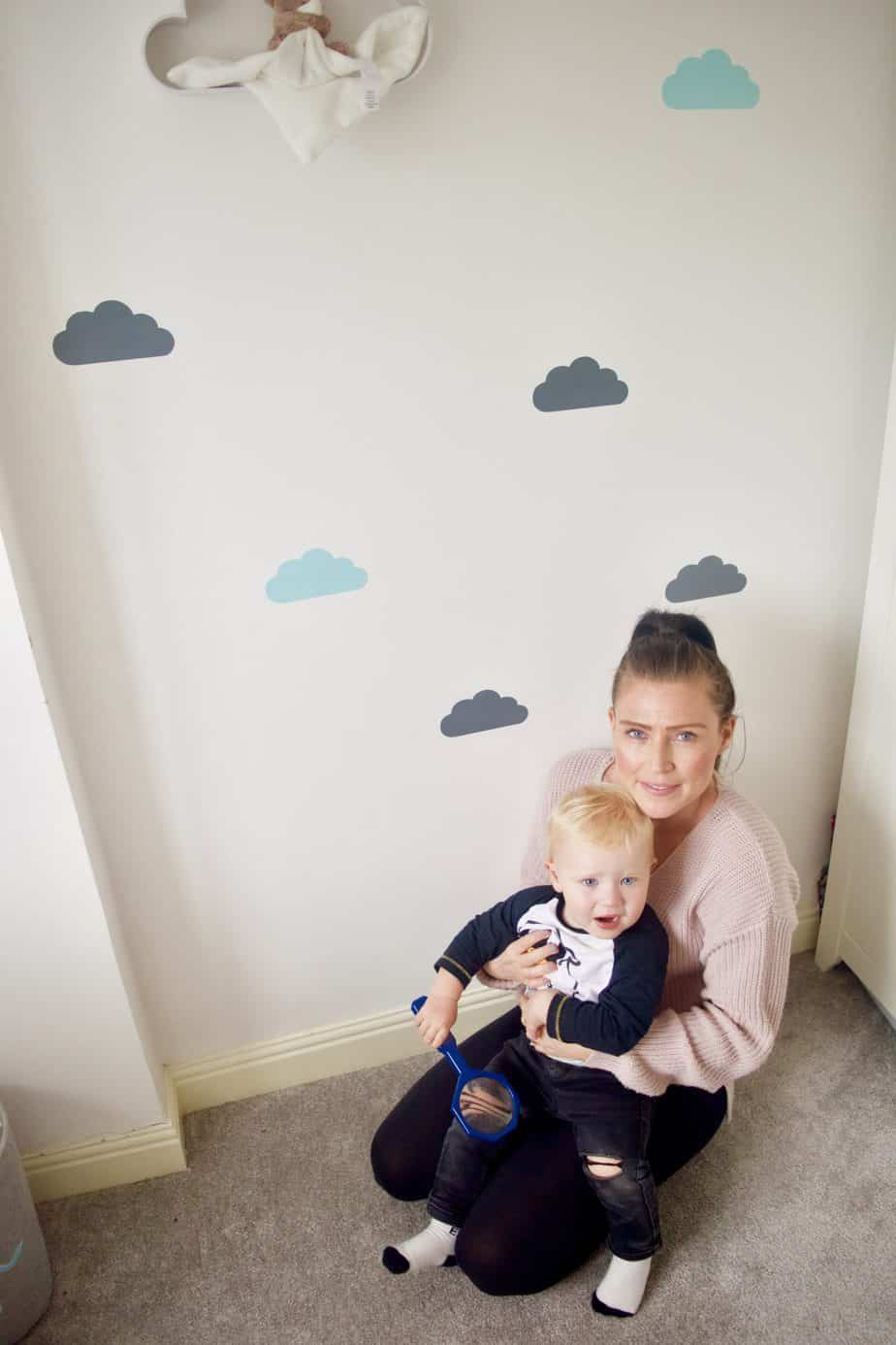 Me and Baby K sitting infront of one wall of cloud shaped stickers for his cloud themed bedroom