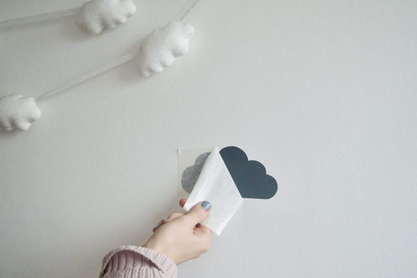 Close up of me peeling off the back layer of the cloud wall sticker for Baby K's cloud themed bedroom