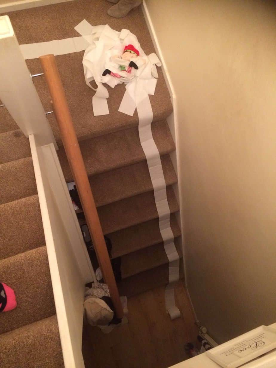 Elf on the shelf having fun with toilet roll down the stairs