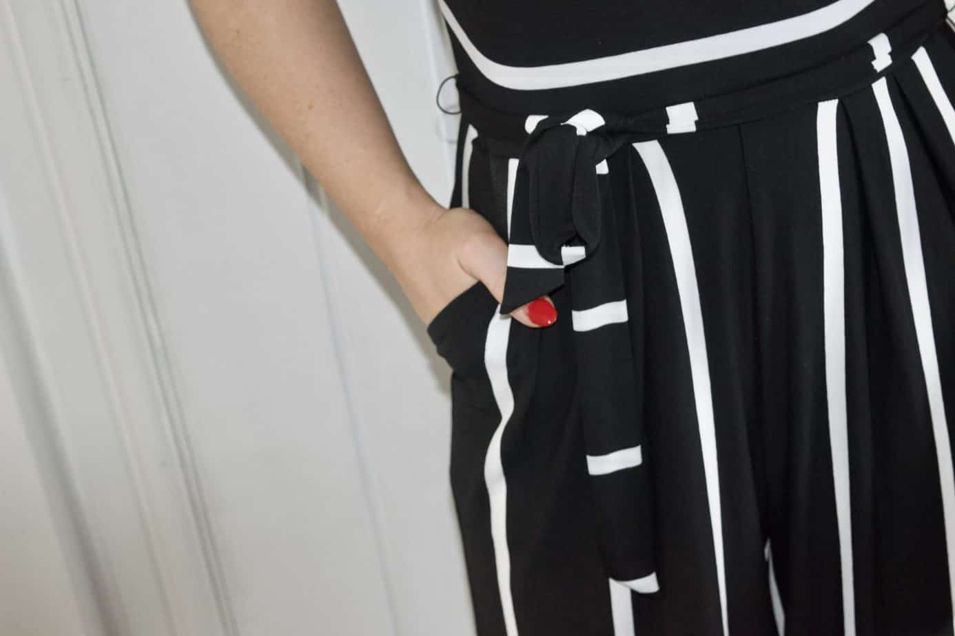 A close up of the black and white stripy fabric with my hand in the pocket of the jumpsuit from popsey clothing