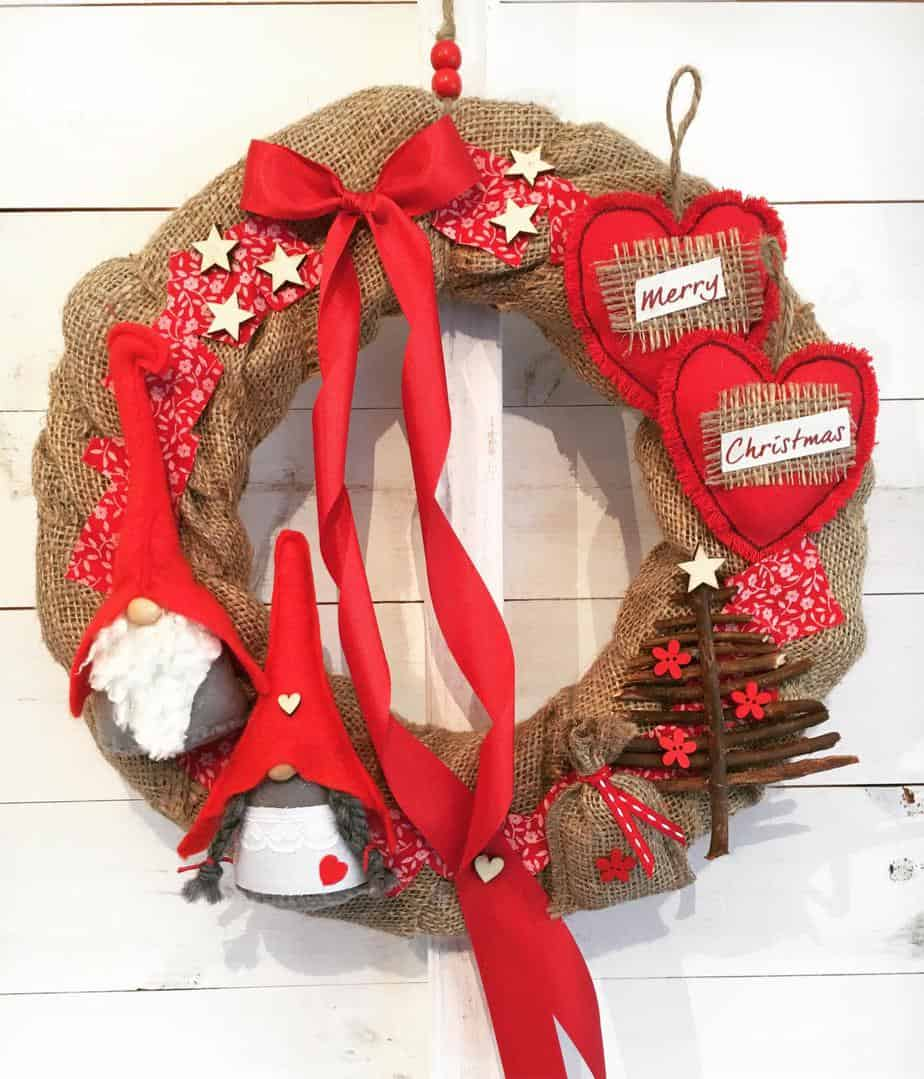 A christmas Wreath from The Grey Company interiors offering red and brown design with santa, bows and hearts
