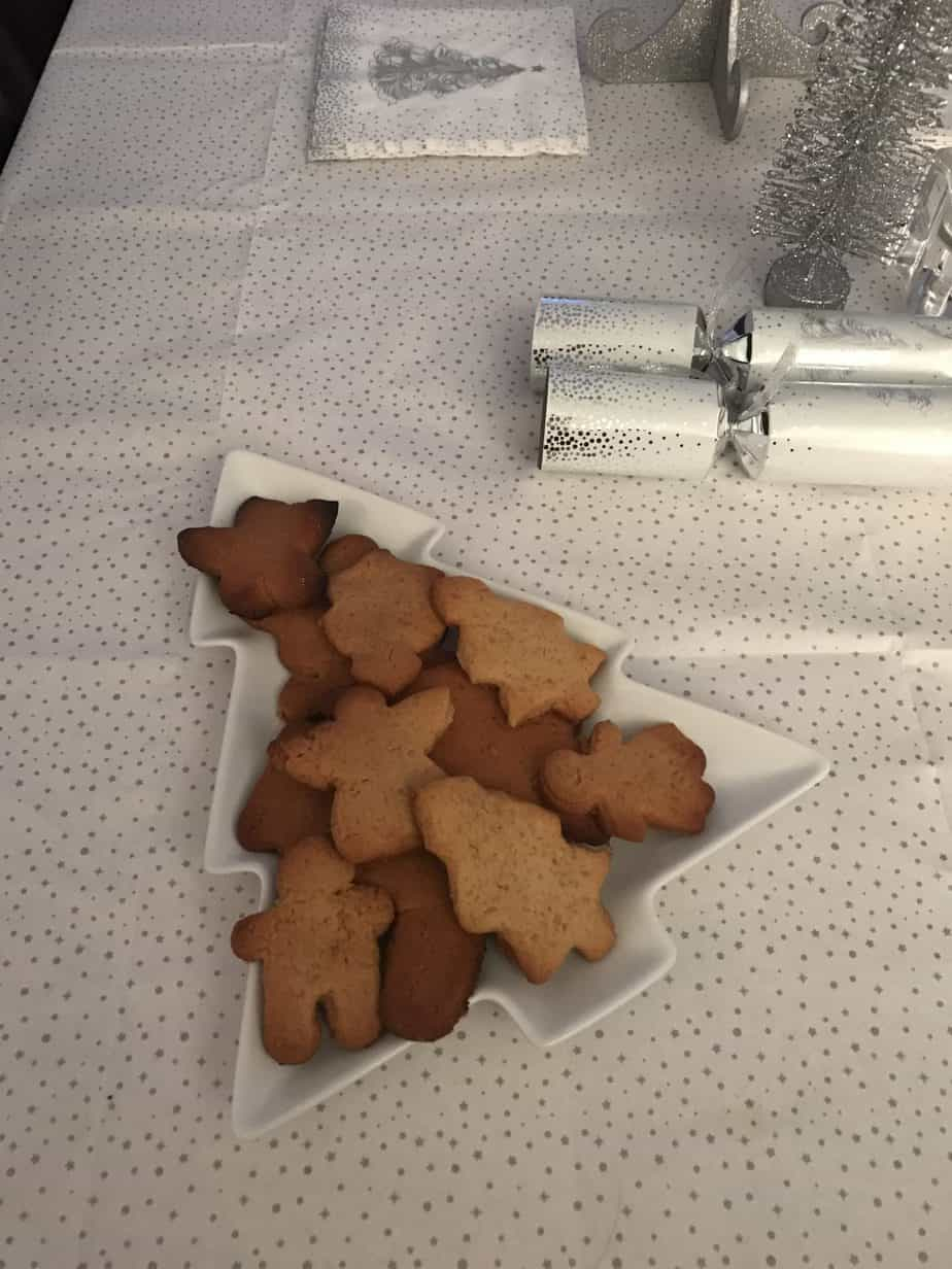 Baking gingerbread or mince pies is a real family christmas tradition each year - christmas tree plate with gingerbread biscuits on it