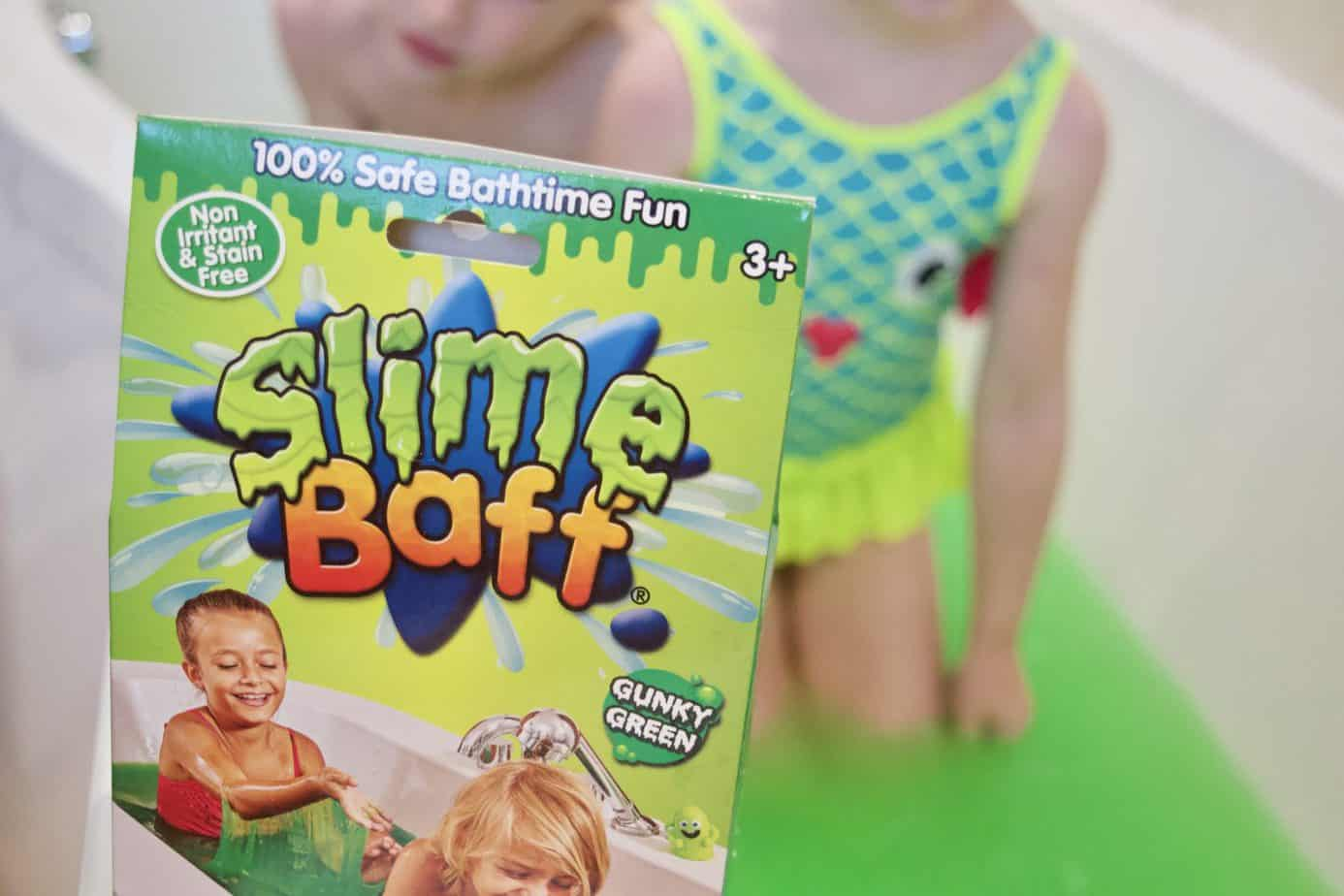 Slime baff packet with the kids in the background in the bath