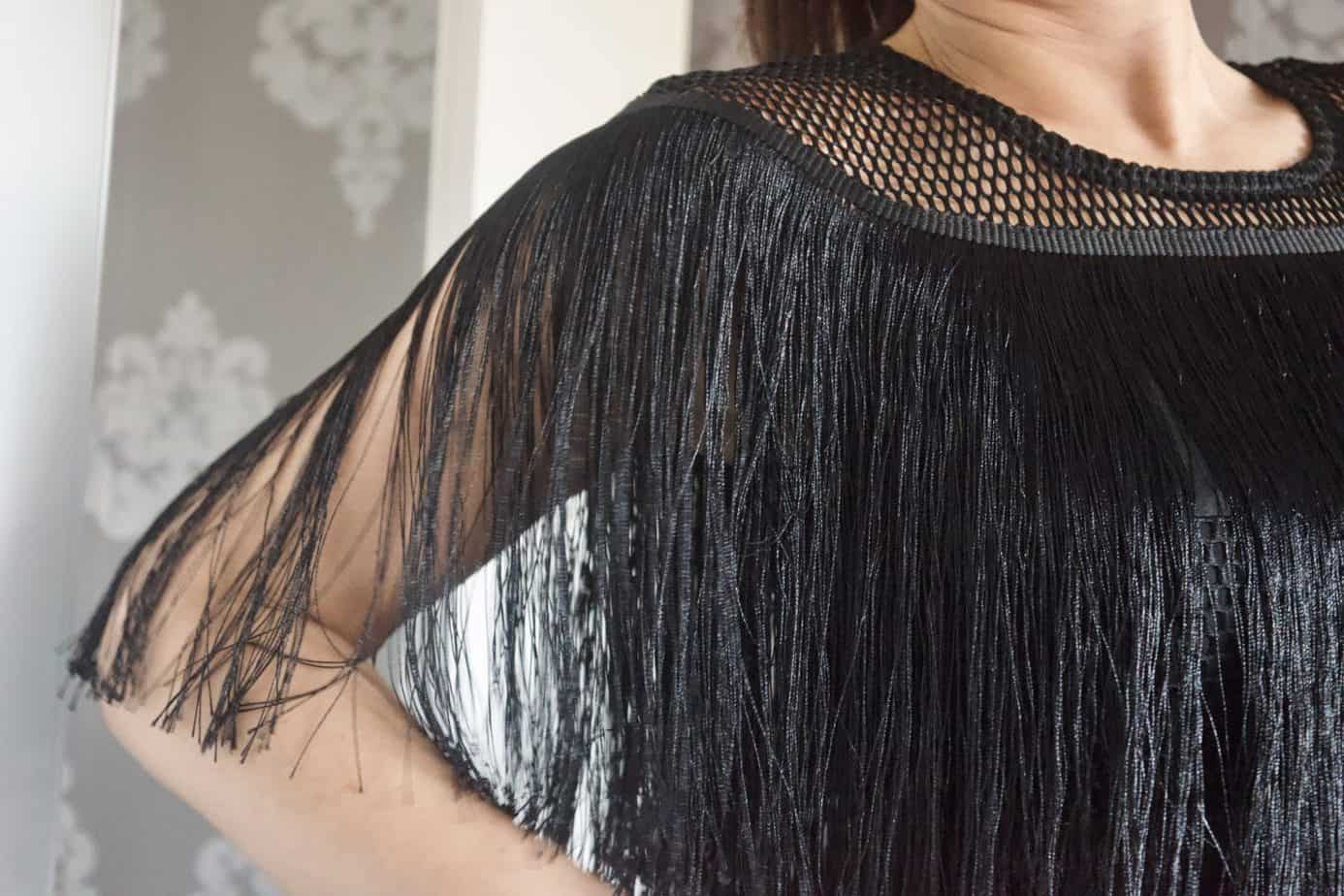 A close up of the top of the dress and tassel detail