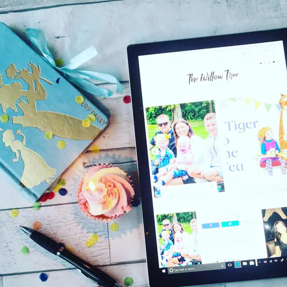 A cupcake, diary, pen confetti and surface pro showing my home page of my blog