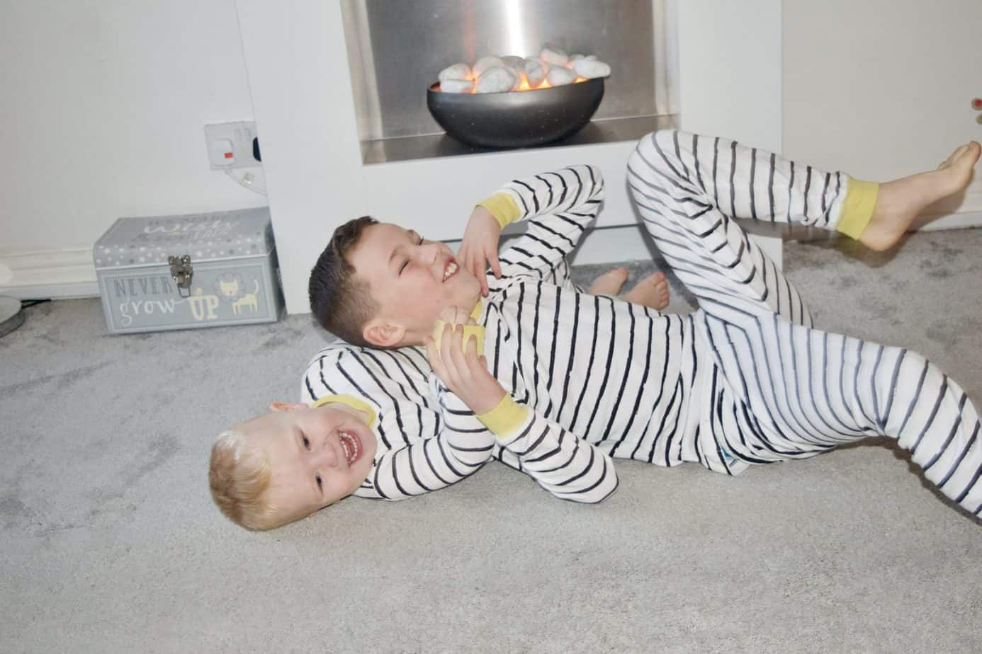 Mr B and Baby K rolling around on the floor wearing their striped pyjamas