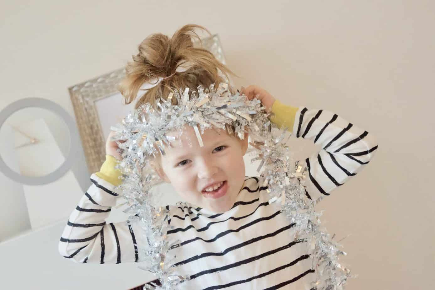 Miss W smiling at the camera with tinsel around her head wearing her organic cotton pyjamas
