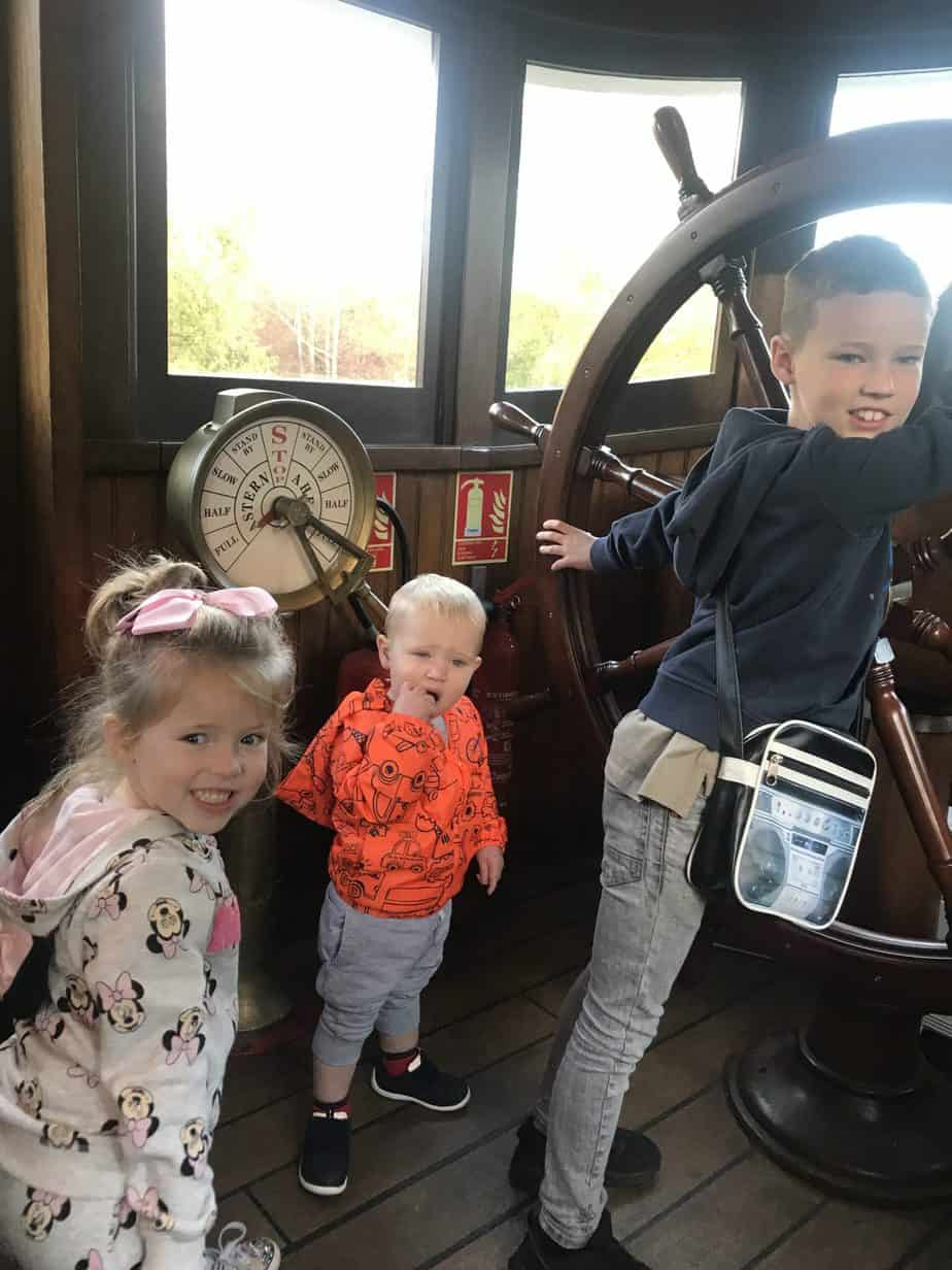 The three kids driving The Molly Brown at Disneyland Paris