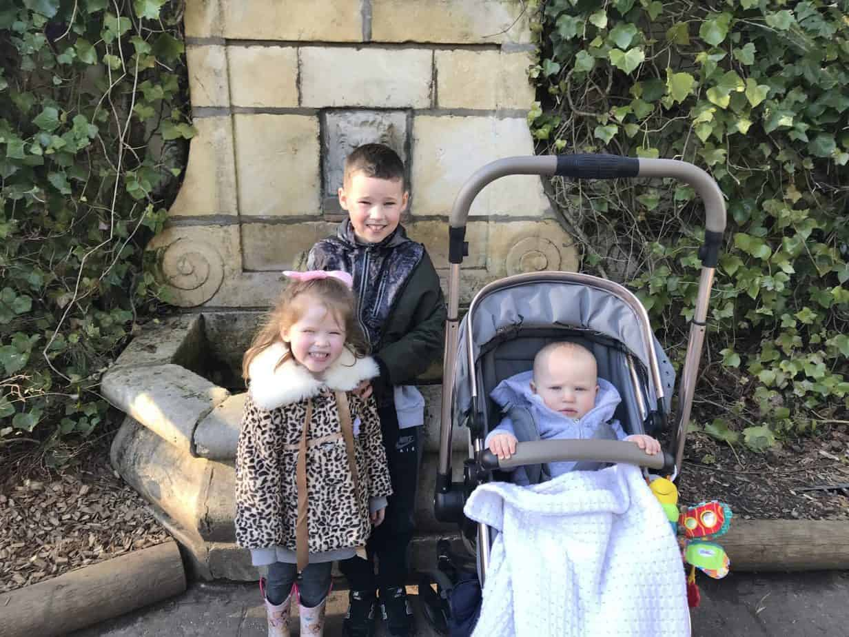 my three children in their warm coats smiling at the camera at Center parcs in my post called what to pack for center parcs