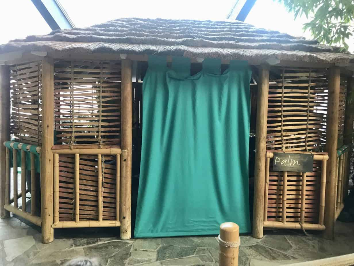 Booking a cabana at Center Parcs - outside of the Palm Cabana which is wooden with a green curtain for the entrance