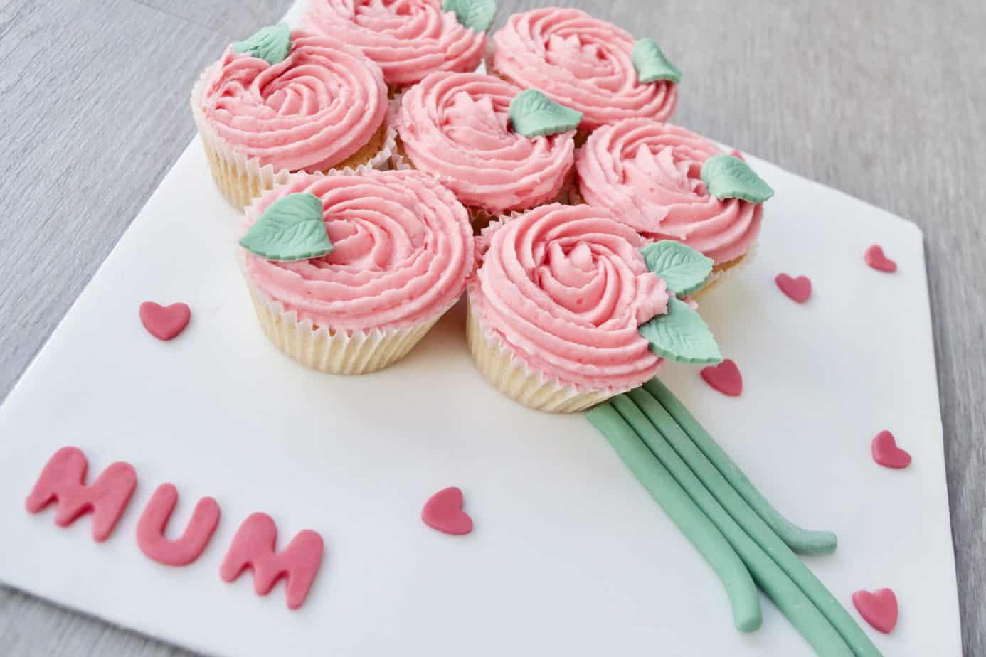 A flower bouquet made out of 7 small cupcakes in pink frosting