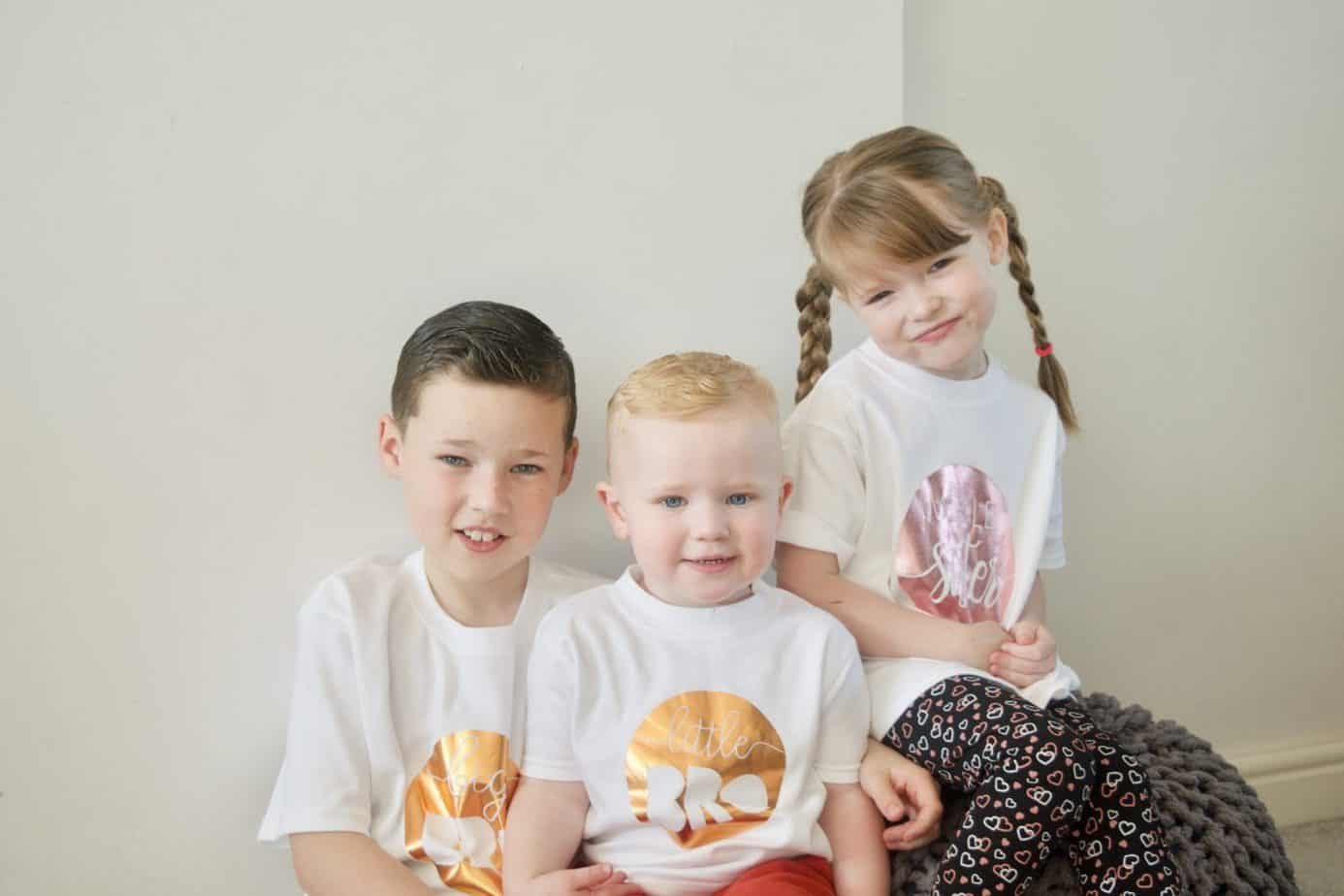All three wearing twinning kids t-shirts from Teether Baby Boutique