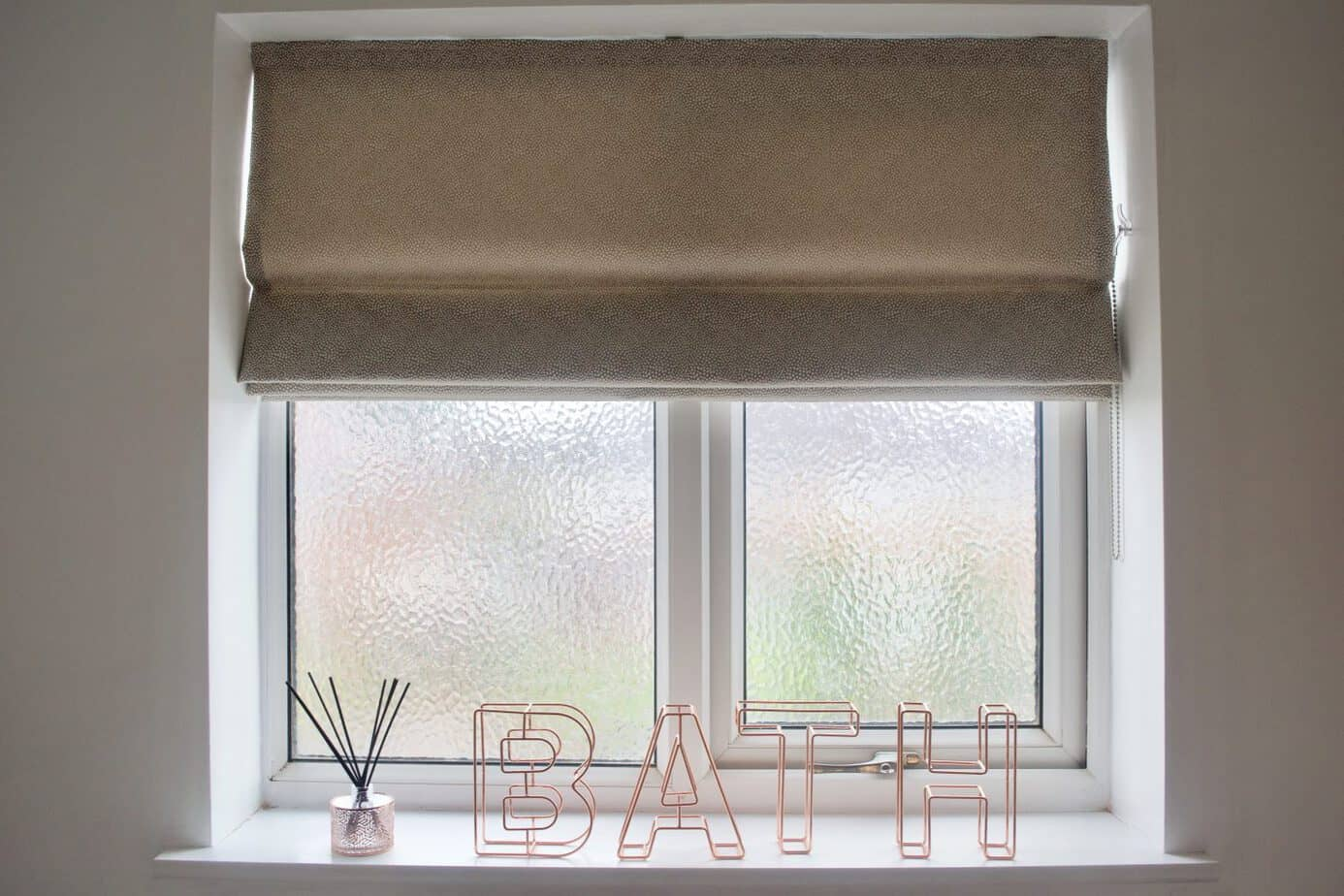 window in bathroom featuring a roller blind from make my blinds