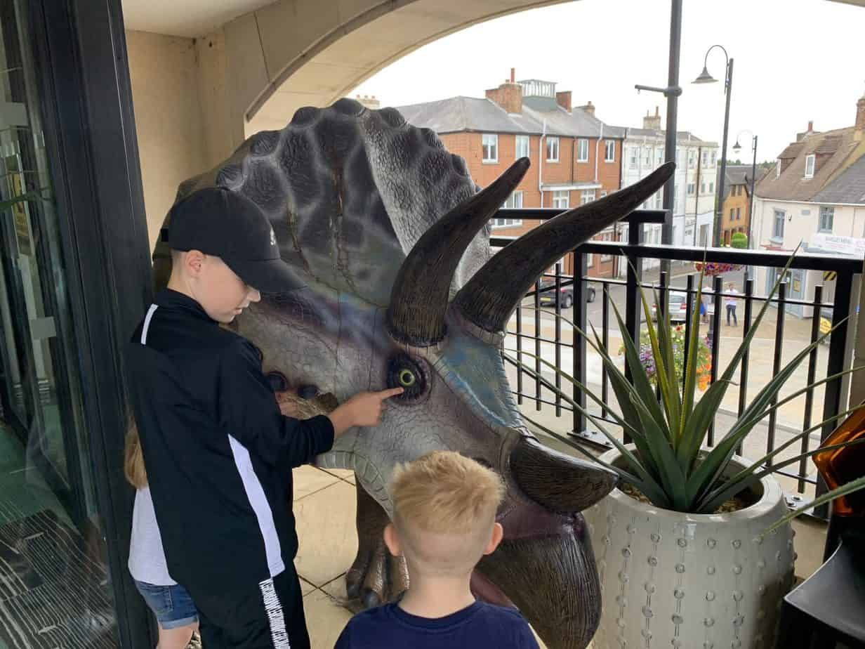 Kids meeting the triceratops on the terrace at jurassic grill