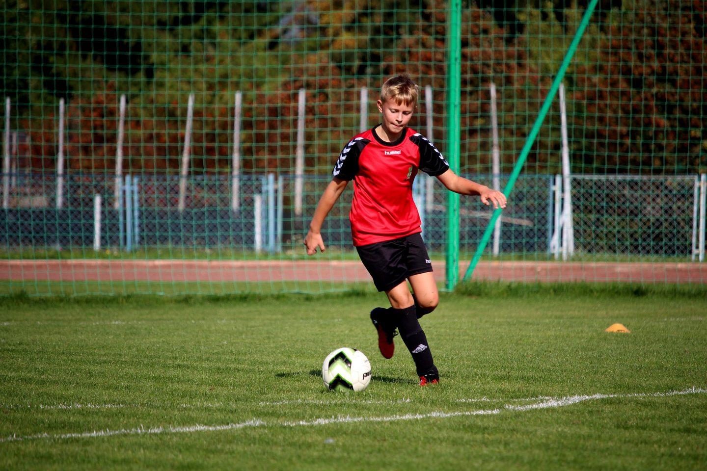 child playing football wearing a red kit
