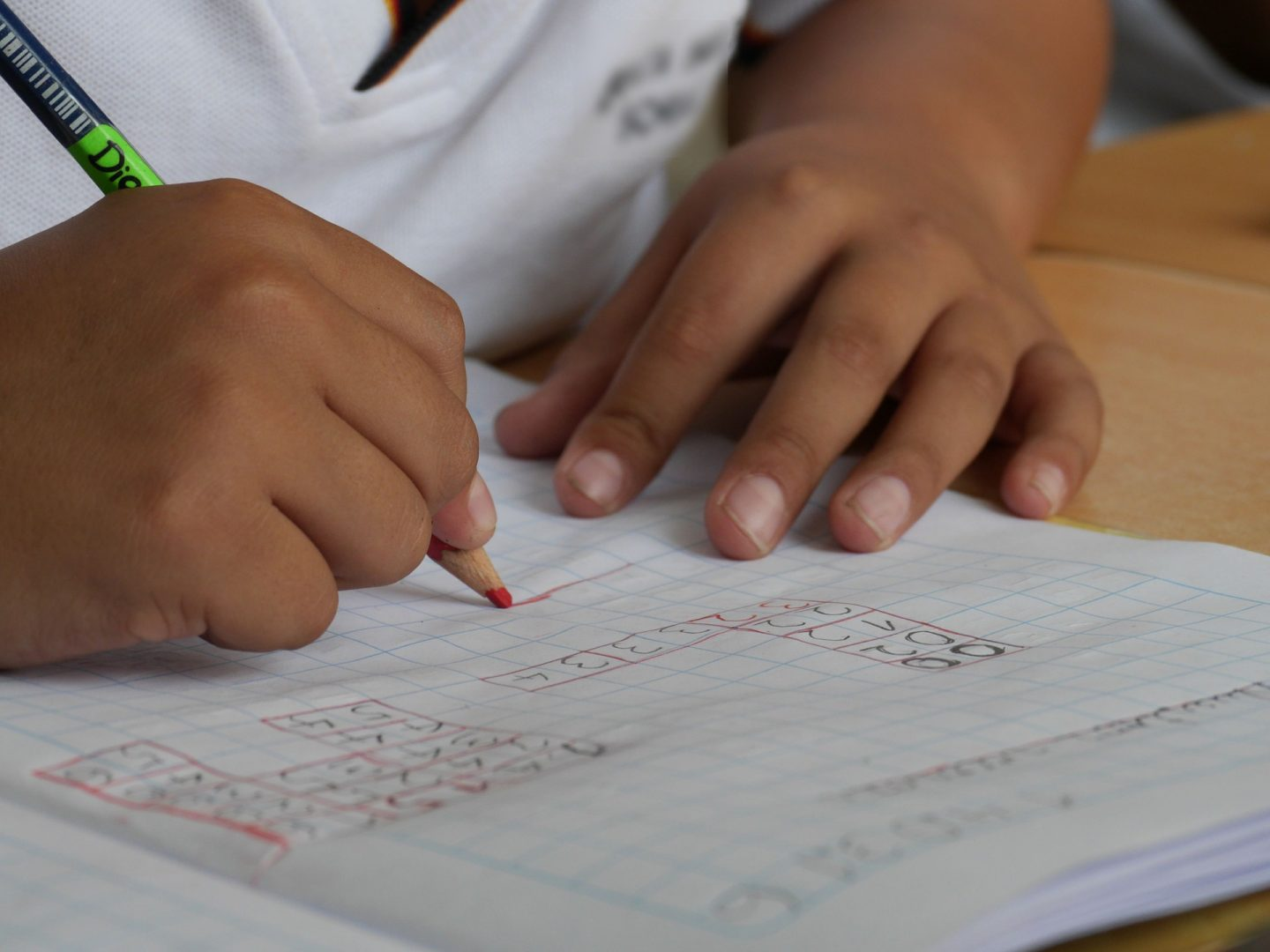 Child writing on a worksheet at school